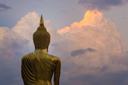 golden standing buddha statue back twilight clouds photo