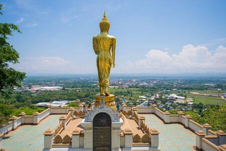NAN  THAILAND APRIL 27 : golden standing buddha statue over the city at Wat Phra That Khao Noi Nan province Thailand on April 27 2015