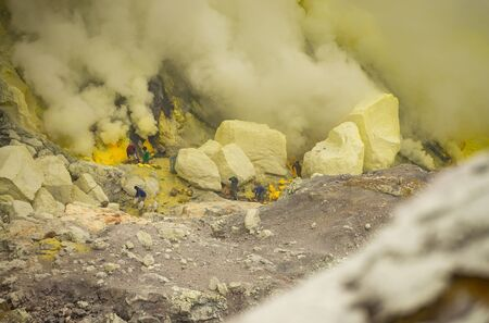 worker carry sulfur for selling at Kawah Ijen volcano crater