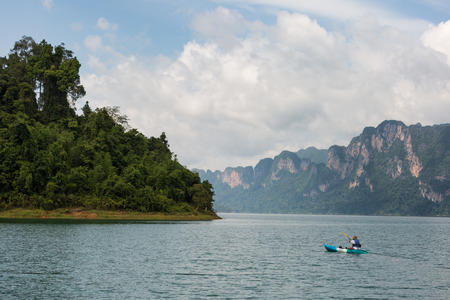 national fruit of china: man kayaking in the sea with lime stone mountain