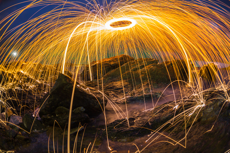 technics: abstract orange light streak dark blue sky rocky beach ,fire steelwool effect technics