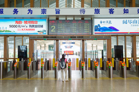 high speed train: SANYA - CHINA, May 13: Unidentified passenger waiting front of station gates at Sanya high speed train station in Hainan, China on May 13, 2015