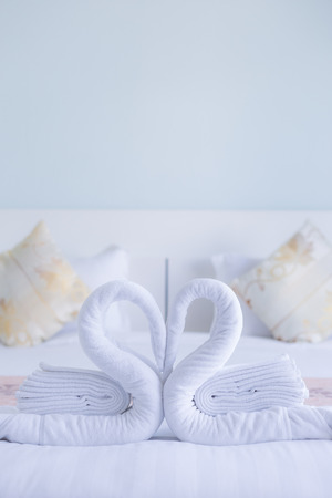 couple bed: cygne blanc en forme de c?ur de serviette tordue sur le lit blanc les jeunes mari�s OFR, soft focus