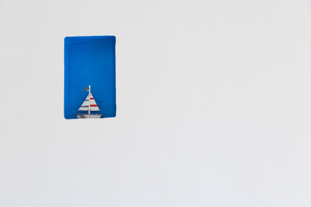wall decor: wooden sail boat decor in white wall, copyspace