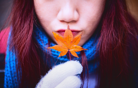 filtered: woman holding orange maple leaf and kiss, vintage filtered color