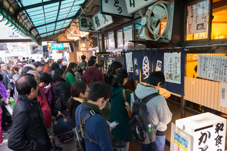 Tourists standing waiting in line front of famous sushi restaurant at outer Tsukiji market, Japan