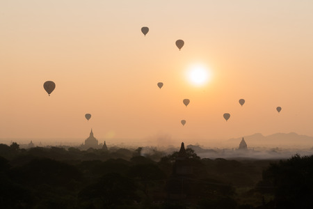Bagan pagoda field with hot air balloons in misty morning golden sun light
