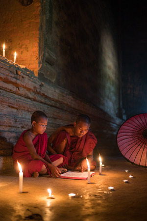 Two myanmar monks sitting on the floor reading scripture book with candle light, vertical composition