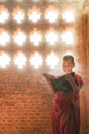 young myanmar monk standing reading scripture warm sunlight with smoke effect Reklamní fotografie