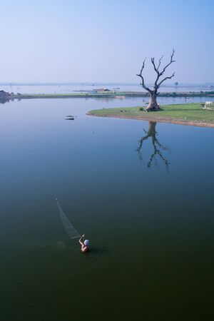 local fisherman using net to catch fish in calm water pond in Myanmar