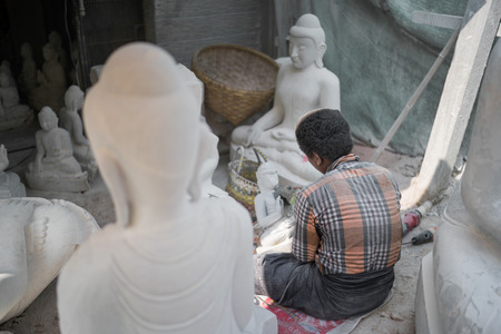 myanmar worker cutting the marble into buddha statue