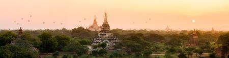 Panorama of Bagan pagoda field with hot air balloons in morning golden sun light