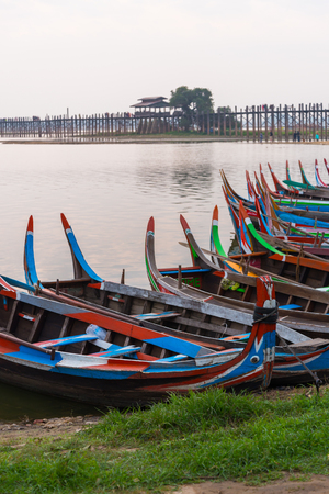 wooden local tourist sight seeing boat front of U Bein wooden bridge in Myanmar