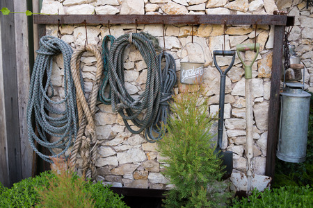 garden tools shovel and rope hanging on the wall