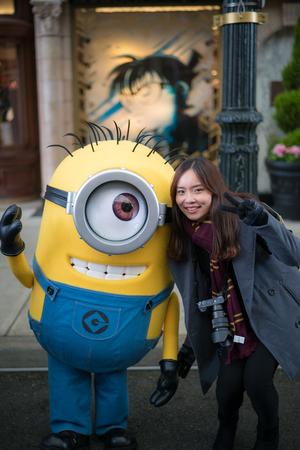 OSAKA, JAPAN - January 14,2017 : Young woman tourist taking photo with Stuart the character mascot from Minions movies Redakční