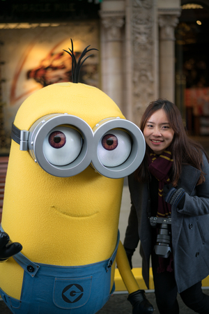 OSAKA, JAPAN - January 14,2017 : Young woman tourist taking photo with Kevin the character mascot from Minions movies