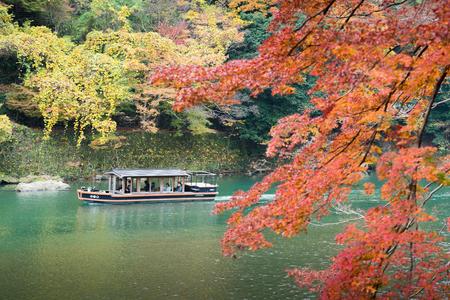 sightseeing tourists boat in Hozu river in autumn season Arashiyama Kyoto, Japan