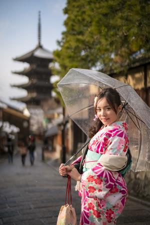 young woman in kimono holding umbrella front of yasaka pagoda