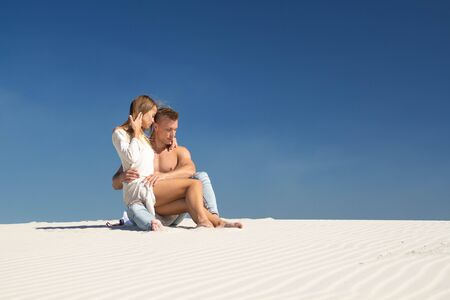 The girl sits on the lap of a man in the sands and gently whispers in his ear Stock Photo