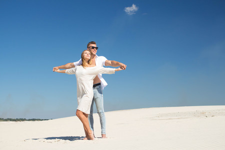 A loving couple holding hands has set a face to the warm sun among white sands Stock Photo