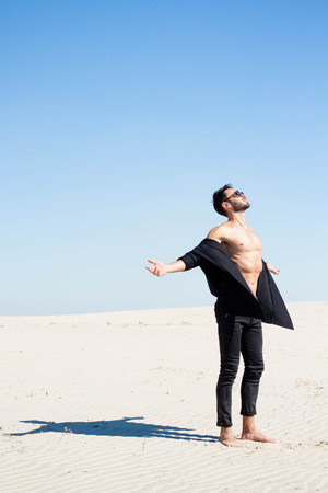A guy in a black unbuttoned shirt is standing on the sand with arms outstretched