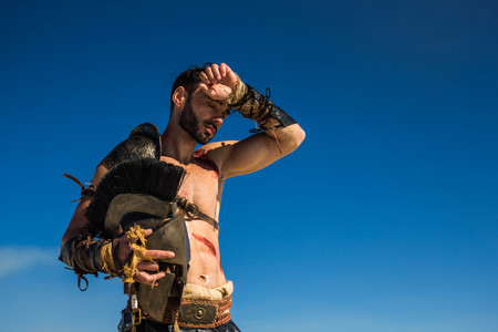 Bloodied tired Spartan warrior wipes the sweat from his forehead. Stock Photo