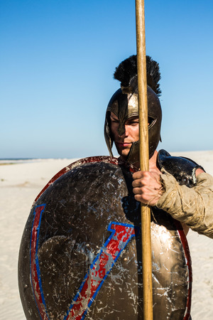 Portrait d & # 39 ; un guerrier spartiate dans un casque avec un bouclier antique et une lance Banque d'images - 81234743