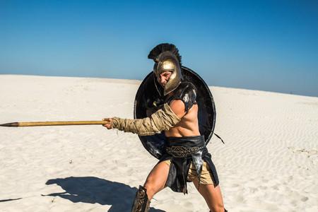 Een agressieve Spartaanse krijger houdt een speer in zijn hand met een gehaakte zak