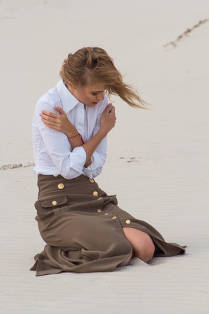 sorrowfully: A girl sits in the wind in the desert and sorrowfully cries Stock Photo