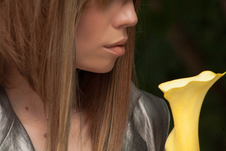 Lips and a girls nose over a beautiful yellow flower Stock Photo