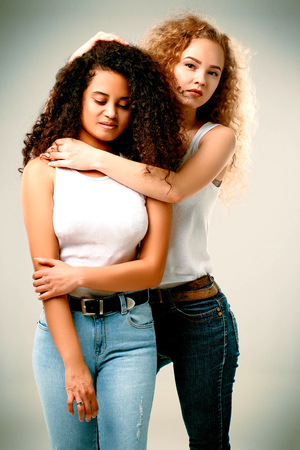 Curly blonde and African American embrace in jeans and white T-shirts Stock Photo