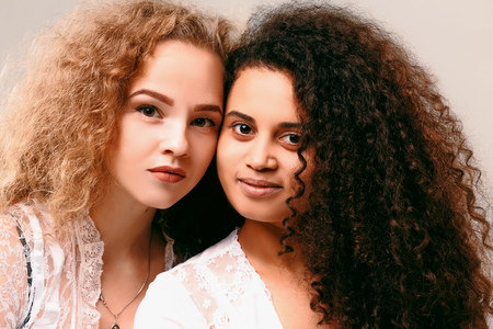 Portrait of two sensual curly girls. Afro and blond