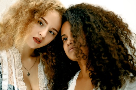 Portrait of two sensual curly girls. Afro and blond Banco de Imagens - 94294396