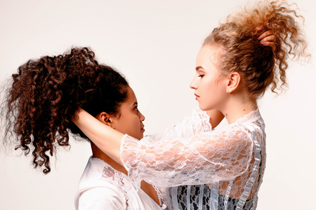 Two beautiful emotional girls drag each other by the hair. Afro and Blond