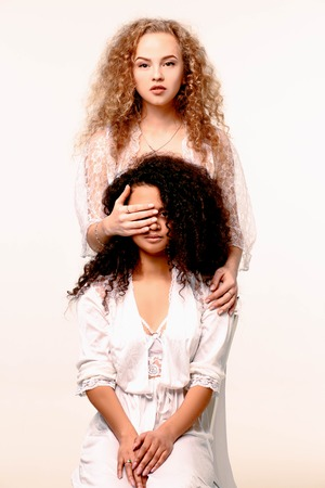 One beautiful serious girl closes her eyes to another. Afro and Blond Reklamní fotografie