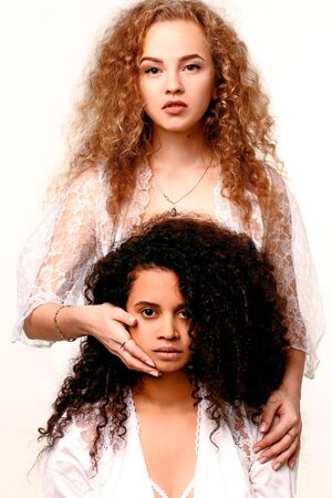 One beautiful serious girl closes her eyes to another. Afro and Blond Stock Photo