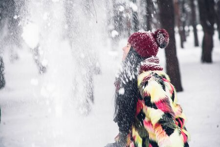 Young beautiful woman having fun throwing snow