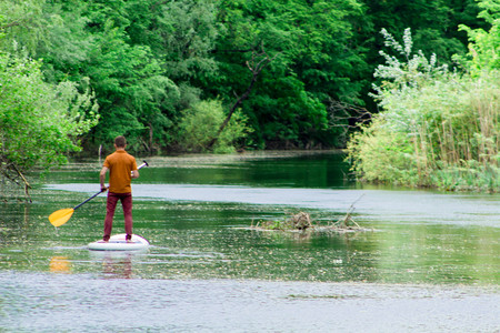 View from the back of a man on a sup board swims along the river Reklamní fotografie