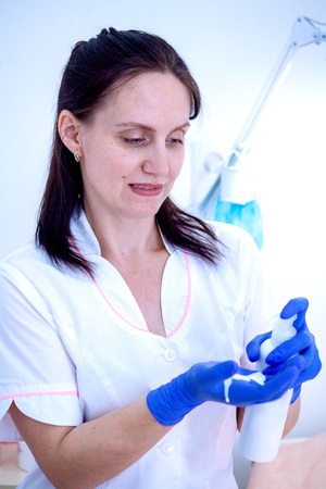 Woman cosmetician in gloves and with cream