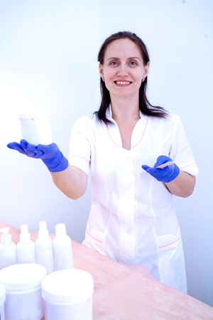 Woman beautician in gloves and with paste for shugaring