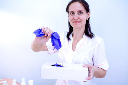 A woman beautician takes the gloves off the box and puts on