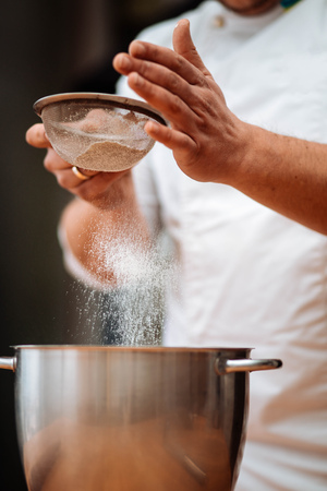 Mens hands chef sift flour in the kitchen