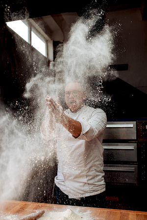 The chef throws flour and cocoa in the kitchen while cooking