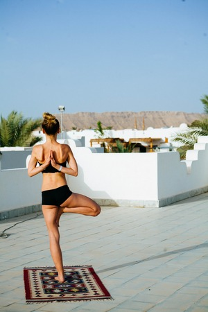 Beautiful young athletic woman doing yoga on the roof with palm trees Reklamní fotografie - 107152694