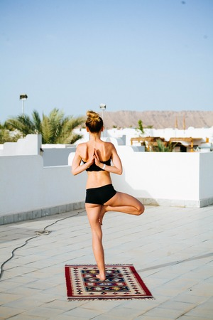 Beautiful young athletic woman doing yoga on the roof with palm trees