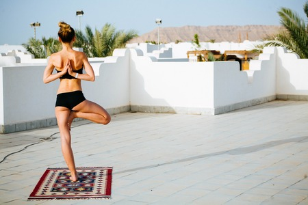 Beautiful young athletic woman doing yoga on the roof with palm trees Stock fotó - 107152697