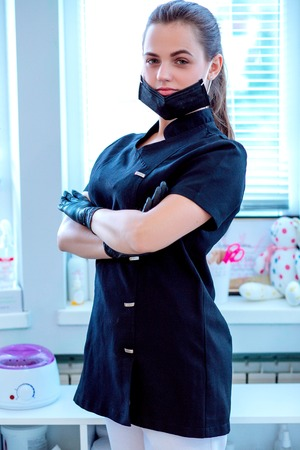 Doctor cosmetologist in a protective black face mask Stock fotó