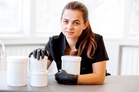 Portrait of a beautician in a black coat, holding a cream jar