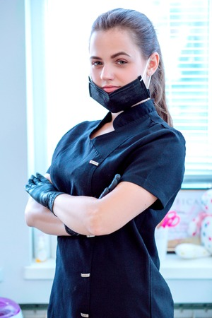 Doctor cosmetologist in a protective black face mask Stock fotó - 122228085