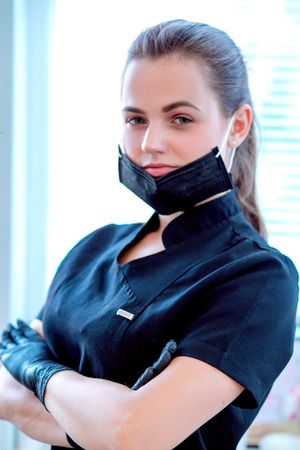 Doctor cosmetologist in a protective black face mask Zdjęcie Seryjne